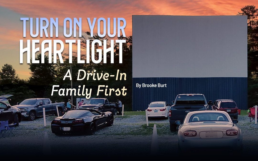 """Drive-in movie theater screen with text """"Turn On Your Heartlight: A Drive-in Family First"""""""